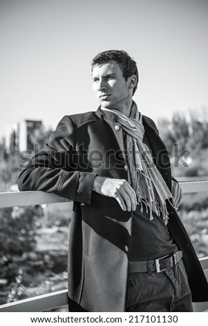 Portrait of a handsome young man wearing jeans, coat and scarf - stock photo