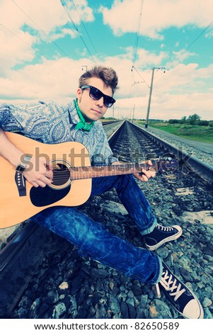 Portrait of a handsome young man with a guitar on a railroad.