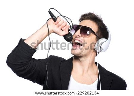 Portrait of a handsome young man with a microphone and headphones on a white background. - stock photo