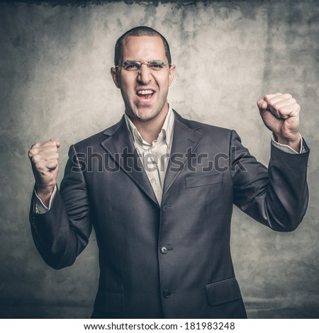 Portrait of a handsome young man with his arms raised in celebration - stock photo