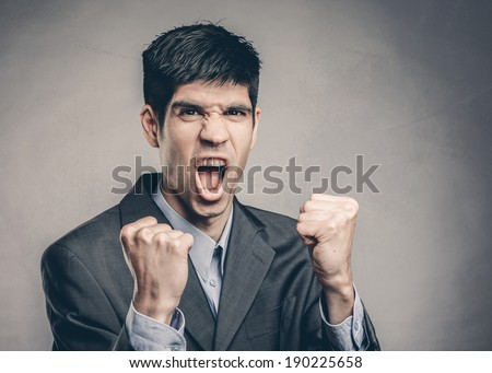 Portrait of a handsome young man with his arms raised in victory - stock photo