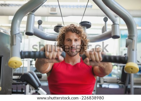Portrait of a handsome young man working on fitness machine at the gym - stock photo