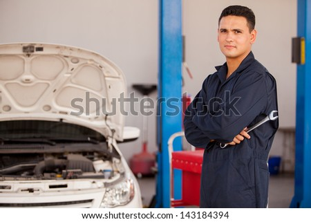 Portrait of a handsome young mechanic holding a wrench and working at an auto shop - stock photo