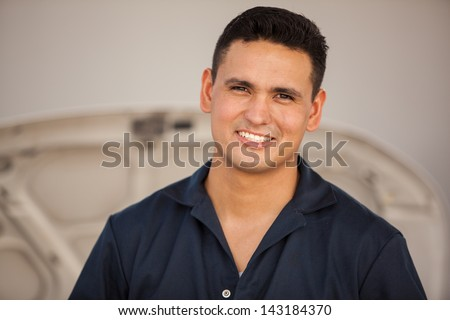 Portrait of a handsome young mechanic working at an auto shop