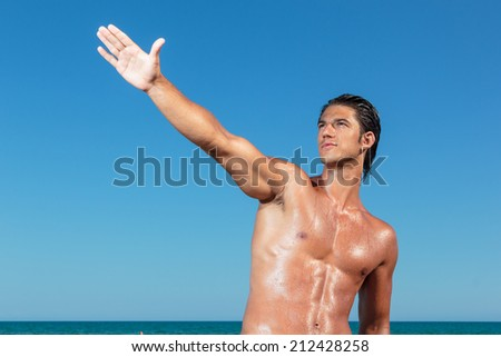 Portrait of a handsome young muscular man in swimwear on the beach - stock photo