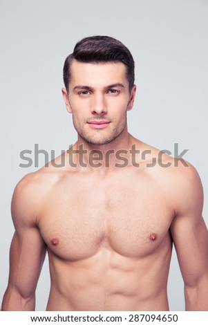 Portrait of a handsome young muscular man standing over gray background. Looking at camera - stock photo