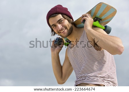 Portrait of a handsome, young, skateboarder, carrying his skateboard on his neck and shoulders, seen from below - stock photo