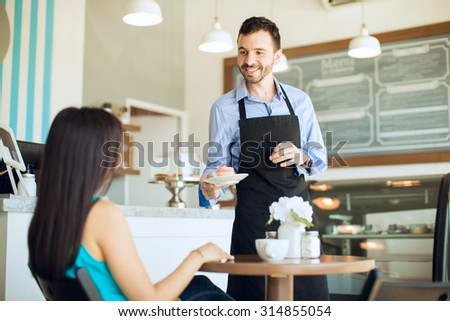 Portrait of a handsome young waiter serving some coffee and a cupcake to a female customer in a cafe - stock photo