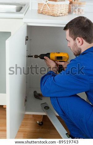 Portrait of a handyman fixing a door in a kitchen