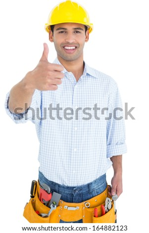 Portrait of a handyman in yellow hard hat gesturing thumbs up against white background