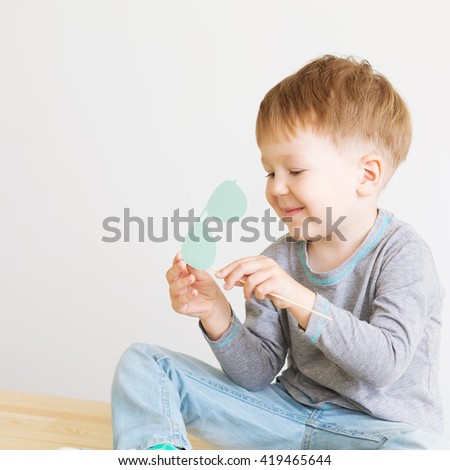 Portrait of a happy adorable little kid with blue paper glasses against a white background. A blind child - stock photo