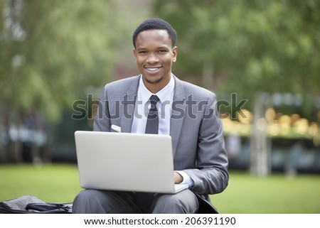 Portrait of a happy African American businessman using laptop in park - stock photo