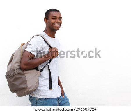 Portrait of a happy african american college student walking on isolated white background - stock photo