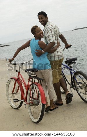 Portrait of a happy African American couple walking with bicycles on the beach - stock photo
