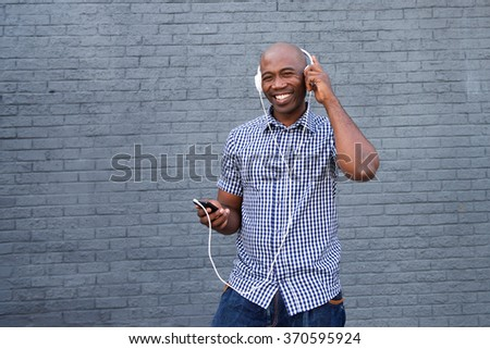Portrait of a happy african american man listening to music with headphones and mobile phone  - stock photo