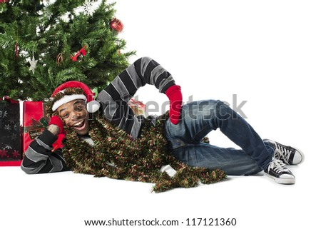 Portrait of a happy African American man lying on his side beside a Christmas tree - stock photo