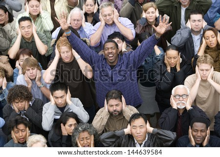 Portrait of a happy African American man raising hands while people covering their ears - stock photo