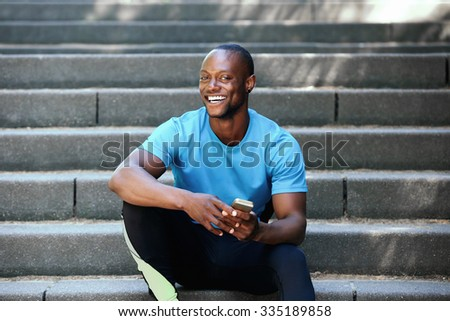 Portrait of a happy african american man sitting on stairs with mobile phone - stock photo
