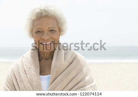 Portrait of a happy African American woman wrapped in towel with sea in the background - stock photo