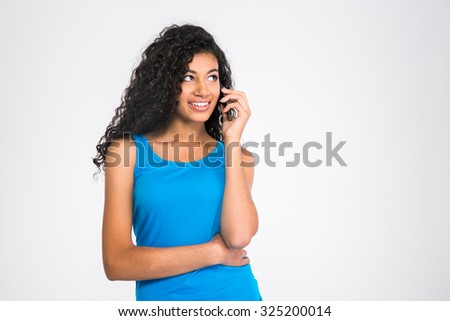 Portrait of a happy african woman talking on the phone and looking away isolated on a white background