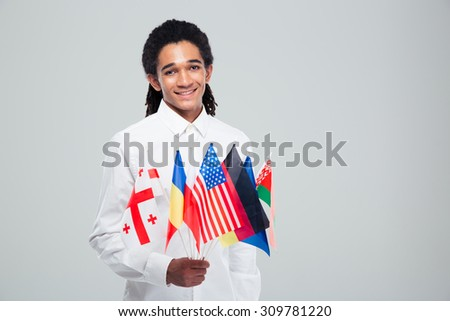 Portrait of a happy afro american businessman holding world flags over gray background - stock photo