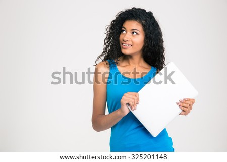 Portrait of a happy afro american holding laptop and looking away on copyspace isolated on a white background - stock photo
