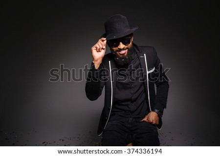 Portrait of a happy afro american man in stylish cloth posing over black background
