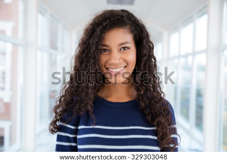 Portrait of a happy afro american woman standing in university hall and looking at camera - stock photo