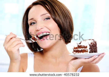 Portrait of a Happy and cheerful beautiful  young woman eats a sweet cake - stock photo