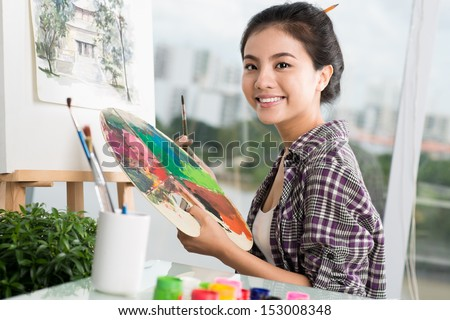 Portrait of a happy artist with a palette in hands on the foreground - stock photo