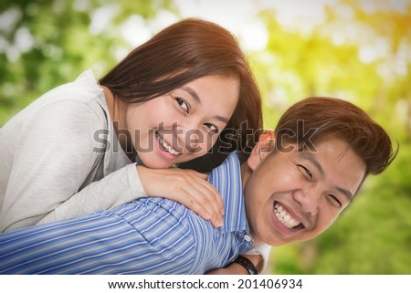 Portrait of a happy asia couple laughing at camera - stock photo