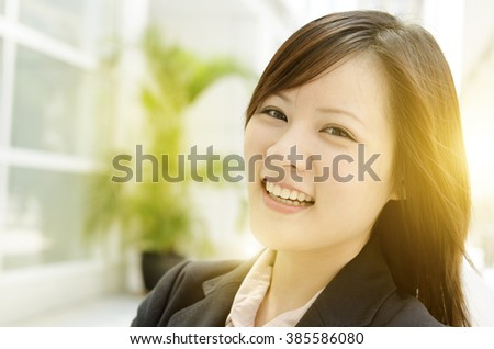 Portrait of a happy Asian business woman smiling and standing at an office environment, beautiful golden sunlight background.