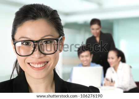 Portrait of a happy Asian business woman with her team in background.
