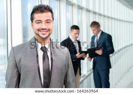 Portrait of a happy asian businessman in a modern office on a background of colleagues - stock photo