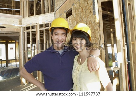 Portrait of a happy Asian couple wearing hard hats at construction site