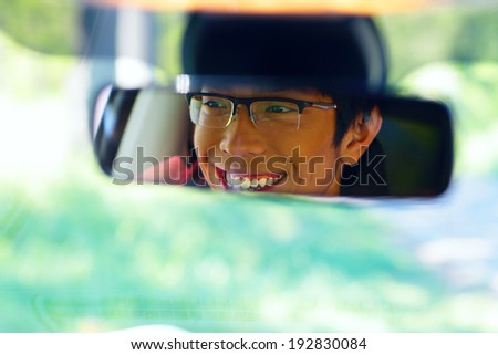 Portrait of a happy asian man sits on driver's seat and Looks in the rear-view mirror - stock photo