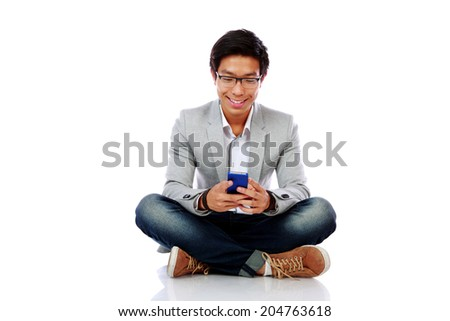 Portrait of a happy asian man sitting on the floor and using smarpthone - stock photo