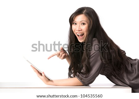 Portrait of a happy Asian woman pointing at her touch screen tablet. - stock photo