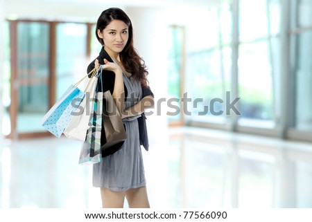 Portrait of a happy Asian woman with shopping bags - stock photo