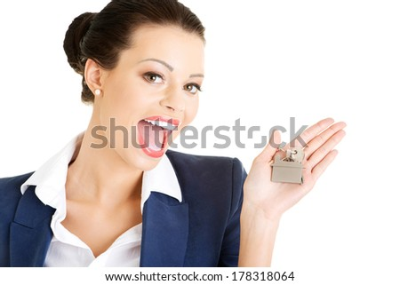 Portrait of a happy attractive caucasian businesswoman, real estate agent, holding a house key against a white background