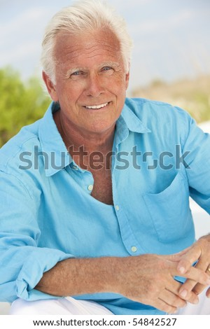 Portrait of a happy attractive handsome senior man sitting down outside and smiling