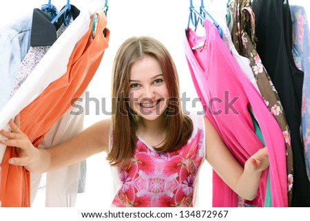 Portrait of a happy attractive teen girl making choices in wardrobe