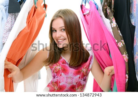 Portrait of a happy attractive teen girl making choices in wardrobe or in shop with clothes