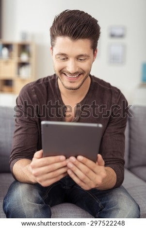 Portrait of a Happy Attractive Young Guy Sitting on the Living Room Couch, Holding his Tablet Computer While Watching Something. - stock photo