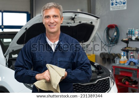 Portrait Of A Happy Auto Mechanic Cleaning Hands With Cloth - stock photo