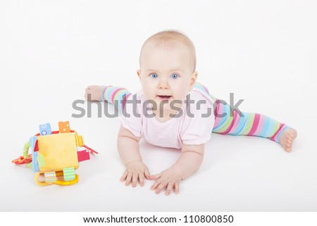 portrait of a happy baby girl on the floor with her toy. studio shot with a white background. - stock photo