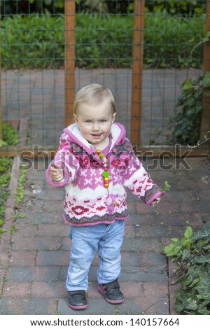 portrait of a happy baby girl playing in the garden