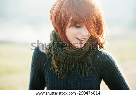 Portrait of a happy beautiful girl with red hair in the field, lifestyle - stock photo