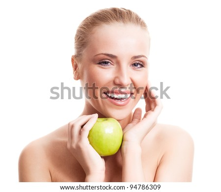 portrait of a happy beautiful laughing woman touching her cheek and holding an apple, isolated against white background
