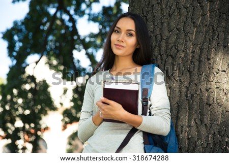 Portrait of a happy beautiful student standing with book outdoors and looking at camera - stock photo